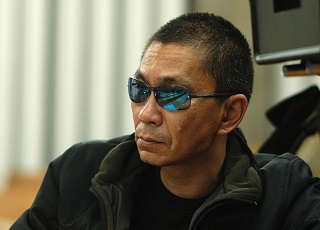 Takashi Miike. That seems to be a camera behind him, so let's assume he's directing right now. (Given the amount he turns out each year, that's statistically quite likely anyway.)