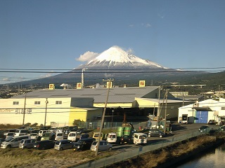 Mount Fuji, taken from the window of a moving train. Which is why all the buildings in the foreground are slanty.