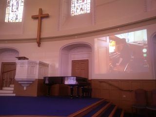 The inside of St Andrew's and St George's West, with Mark Spalding visible on the screen to the right